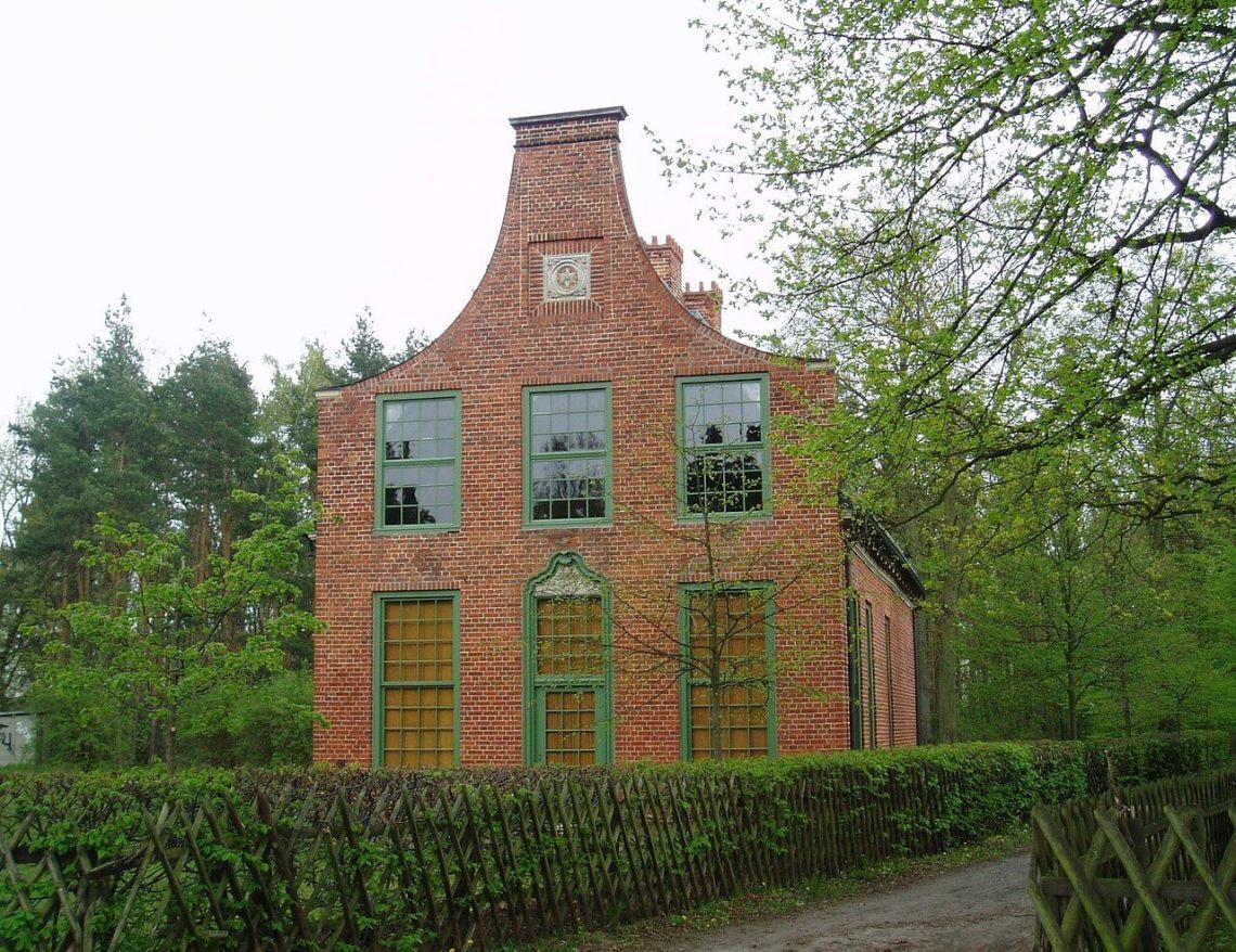 Bakstenen huis met groene roedevensters in groene, bosrijke omgeving
