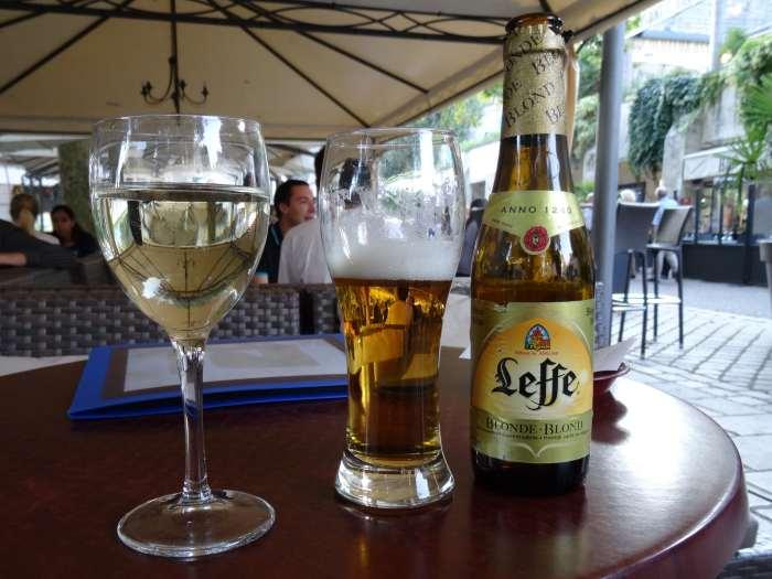 Glas witte wijn en Leffe blond op terrastafel