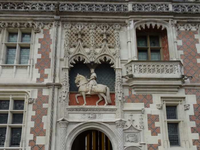Ruiterbeeld boven de ingang omringd door gouden lelies en gotische decoraties