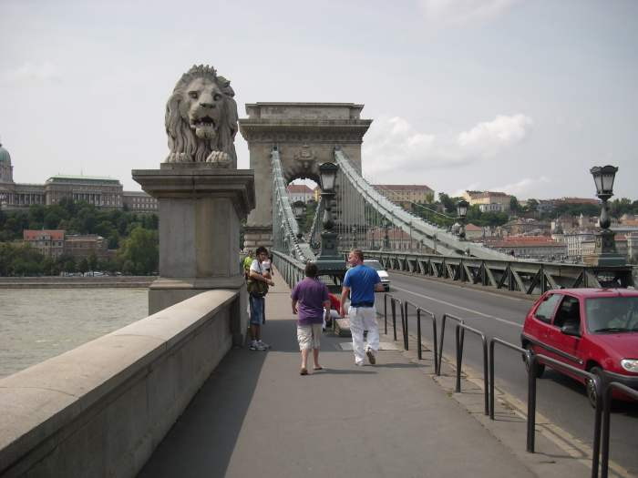Stalen kettingbrug met stenen leeuw en koninklijk paleis op de achtergrond