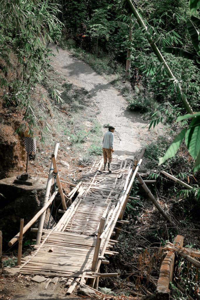 Villageoise traversant un pont de bambou dans les chemins autour de Munduk