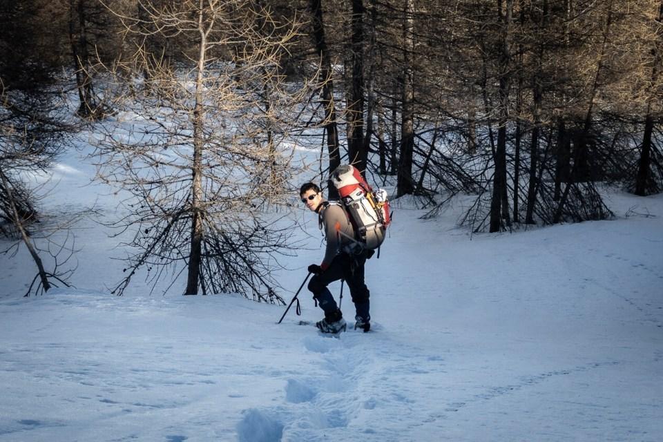 Jeune homme avec sac à dos en randonnée en raquettes en forêt