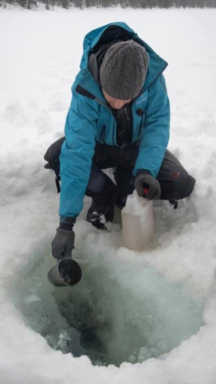 Puisage d'eau à travers un trou dans le lac gelé