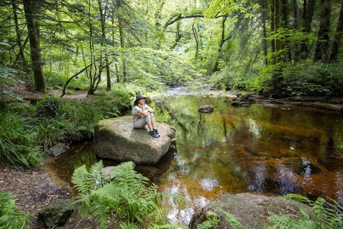 Femme assise au bord de la rivière d'Argent dans la forêt d'Huelgoat