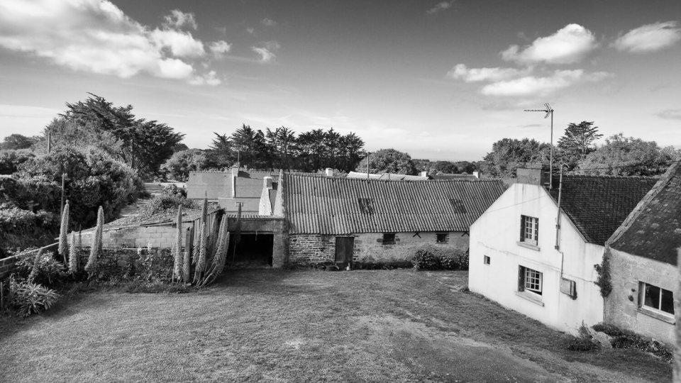 Photographie en noir et blanc d'un groupe de maisons traditionnelles bretonnes
