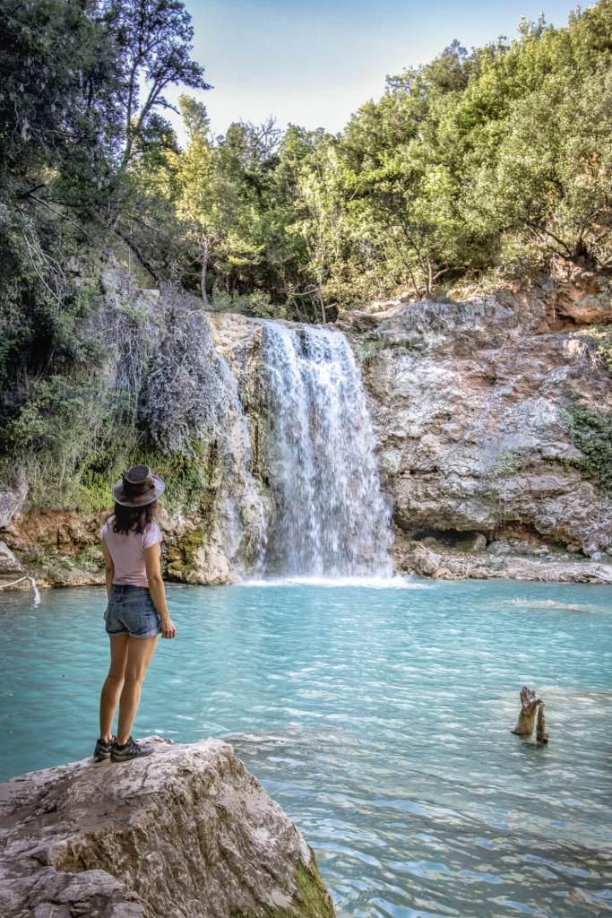 Femme se tenant debout sur un rocher devant la deuxième cascade de Sillans