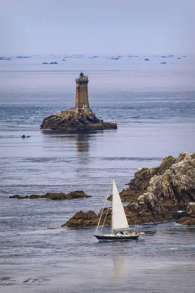 Voilier à la pointe du raz avec le phare de La Vieille en fond