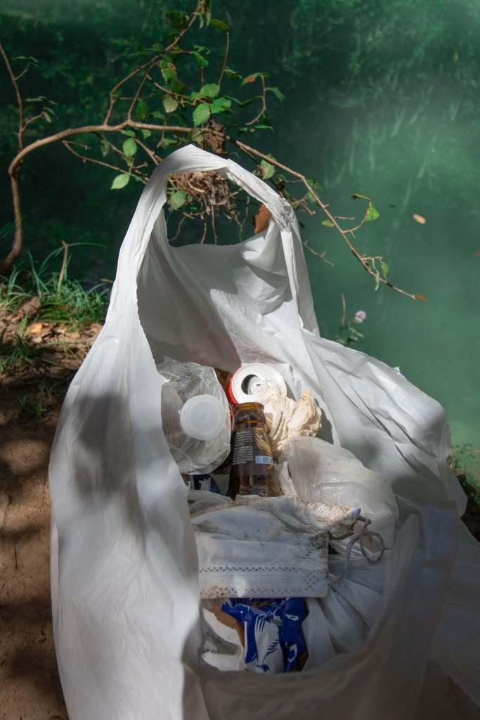 Sac plastique contenant des déchets ramassés près de la cascade de Sillans