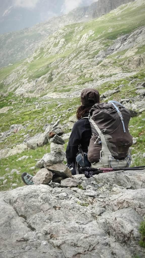 Je suis assise sur un rocher en montagne près d'un cairn, avec mon sac à dos