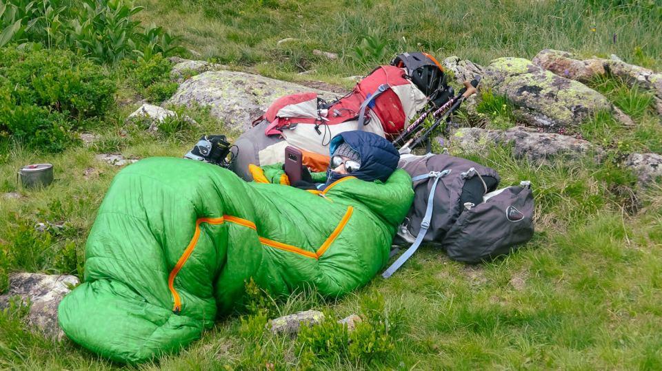 Je suis emmitouflée dans mon duvet avec ma doudoune, allongée dans l'herbe