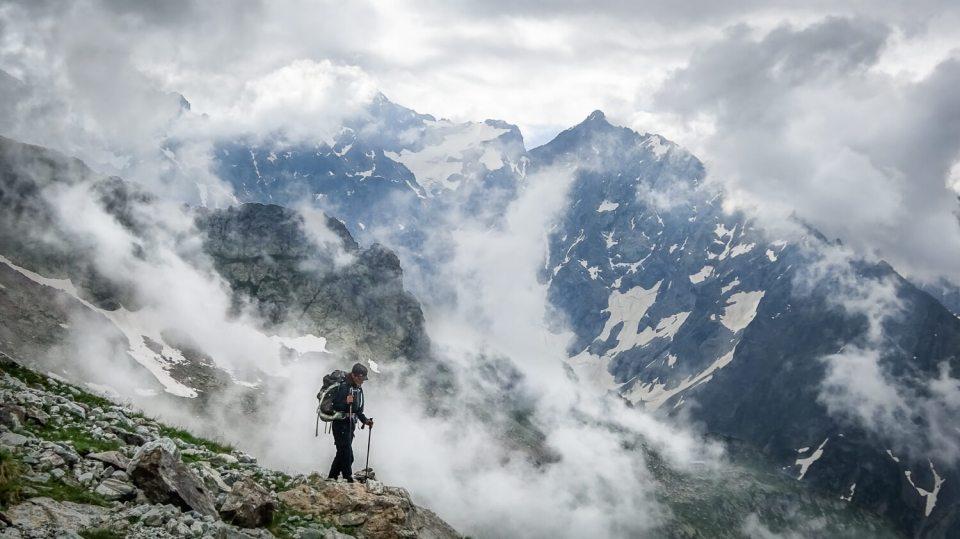 Marcheuse en montagne dans les nuages, avec bâtons de marche