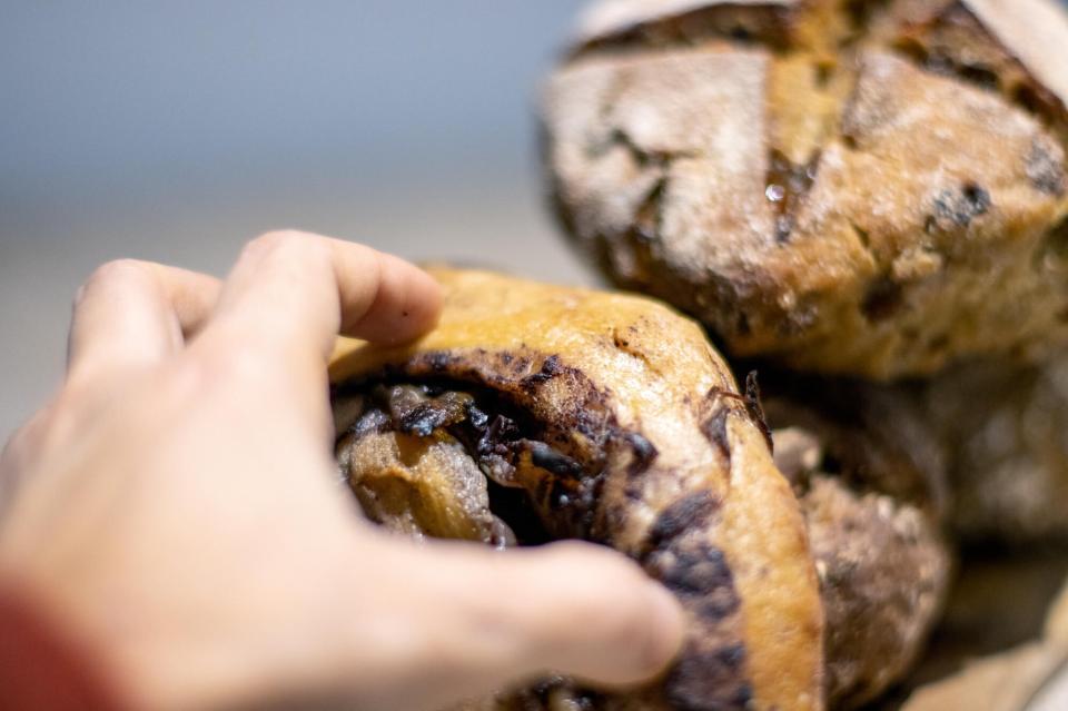 Main saisissant un pain roulé aux olives et oignons confits