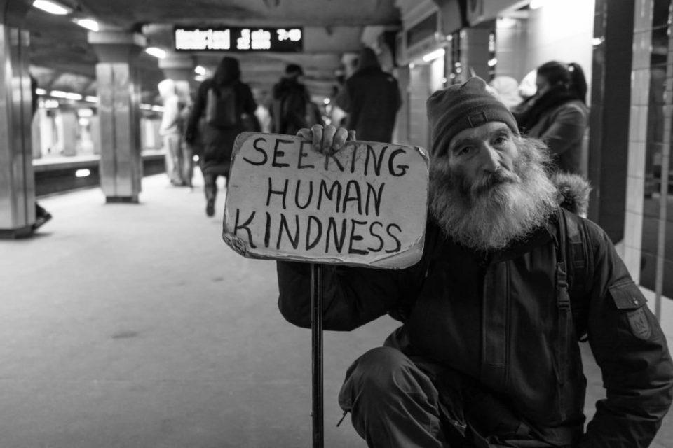 "SDF qui tient une pancarte ""seek human kindness"""