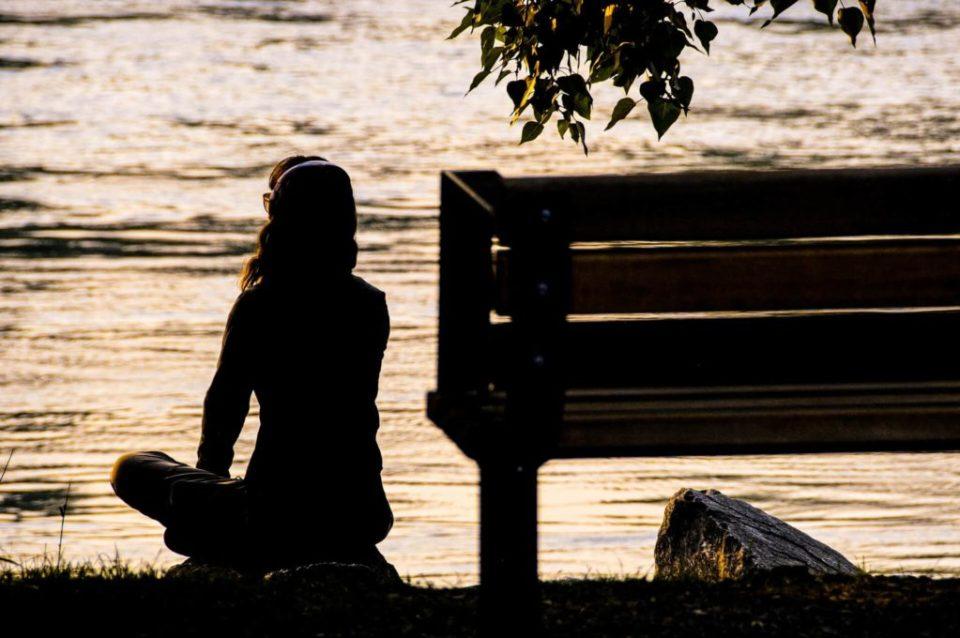 Jeune fille avec casque audio assise en tailleur devant un lac