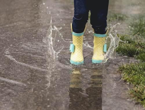 Un enfant saute dans une flaque en bottes de pluie