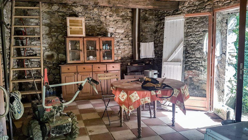 Intérieur du mazet pièce principale avec buffer de cuisine et table en bois