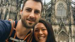 anya and phil smiling at the camera with the cologne cathedral behind them. Cologne was a stop on the Eurovelo 15.