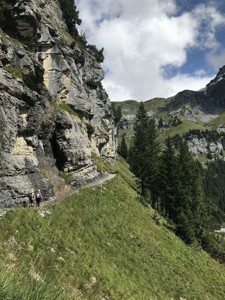 picture of oeschinensee hiking - mountains and greenery in the foreground, with a blue sky in the background.