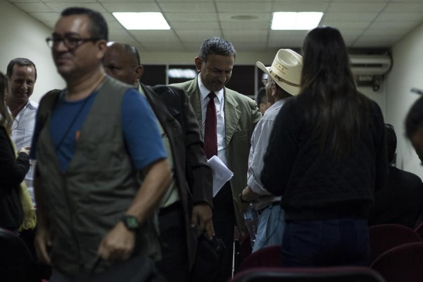 The lawyer Rodolfo Garay Pineda (in olive green jacket with red tie), defense counsel for two colonels accused for the Mozote massacre, speaks with the witness Genaro Sánchez during a pause in a hearing on September 28 in the courtroom in San Francisco Gotera, Morazan. Photo by Víctor Peña for El Faro.