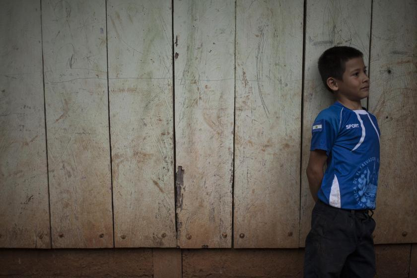 A child poses in the home of Orlando Márquez in El Mozote. The exhumations of the Márquez family took place in 2012, two years after Orlando found the bones of his siblings and his parents. Like the witnesses returning to tell their tragedies in the courtroom, the earth of the nearby towns and villages also brings the victims to the surface. Photo by Víctor Peña for El Faro.