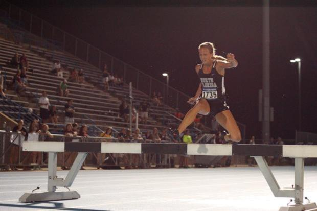 UNF's Elle Baker jumps over one of the four hurdles during the steeplechase race. Photo by Joshua Brangenberg.