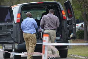 Officials remove Louissaint's body from the scene.Photo by Julianne Brugger
