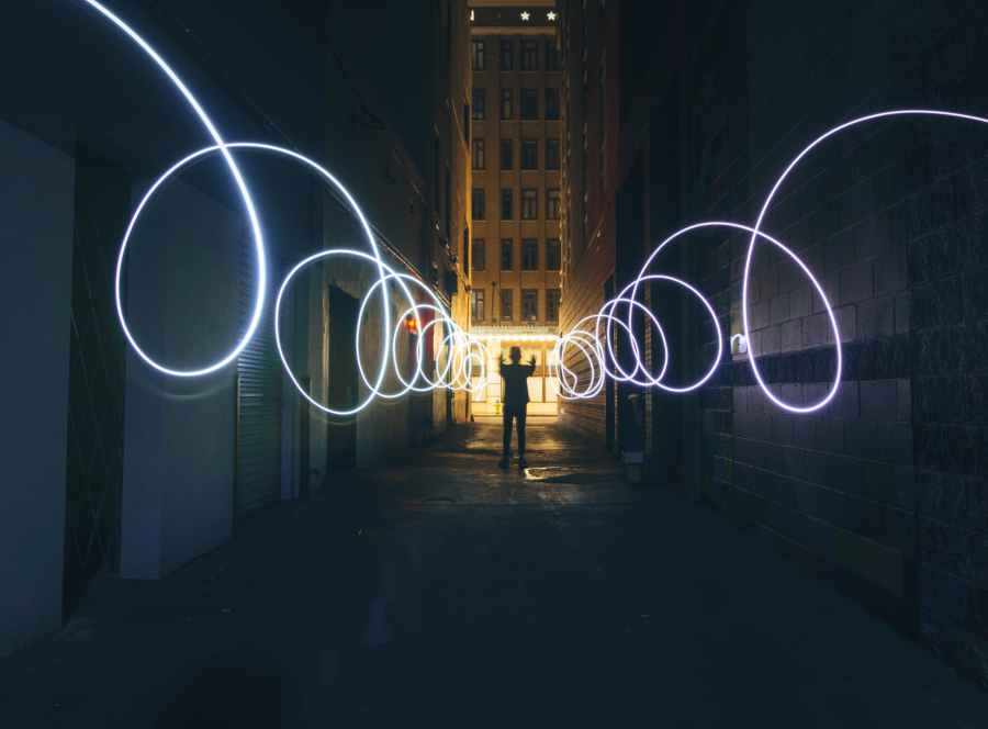 silhouette of person making circles with flashlight on dark street