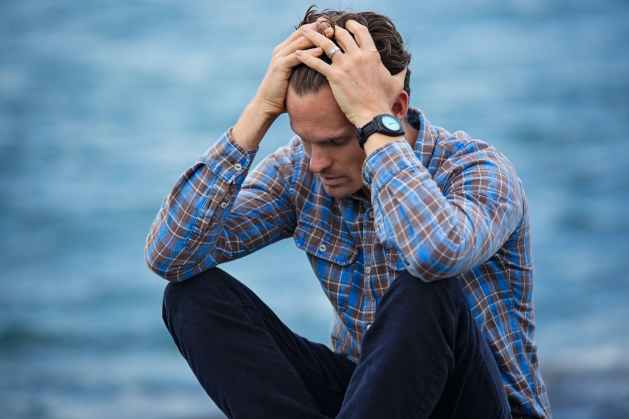 man in blue and brown plaid dress shirt becoming present with hands on head expressing feelings of sadness