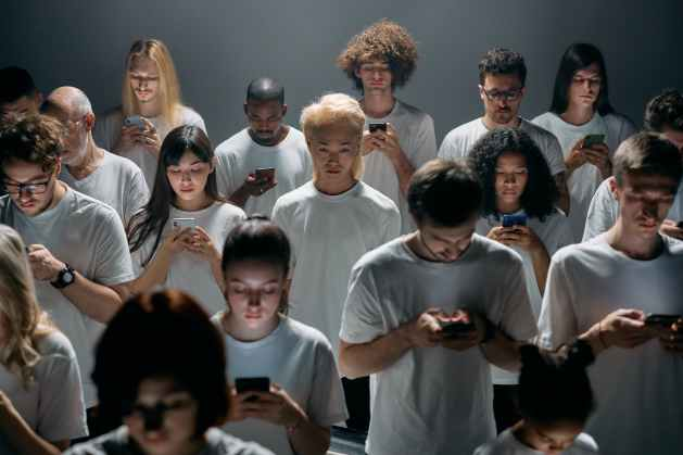 group of people in white shirts staring at their phones in which they need to learn how to transcend time rather than being controlled by it