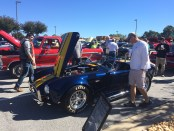 Car enthusiasts inspect a 1966 Shelby Cobra Roadster (Photo by Ariana Cervantes)
