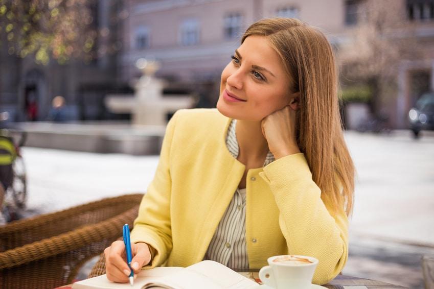Eine junge Frau mit langen blonden Haaren sitzt auf einem Stuhl auf einer Terasse und lächelt, träumt vor sich hin. Sie macht einen glücklichen und nachdenklichen Eindruck, denn damit strahlt sie vollstes Selbstvertrauen aus. Sie trägt eine gelbe Bluse und schreibt mit einem blauen Stift in ein Notitzbuch. An der Seite steht eine Tasse Kaffee welchen sie schon zur hälfte ausgetrunken hat.