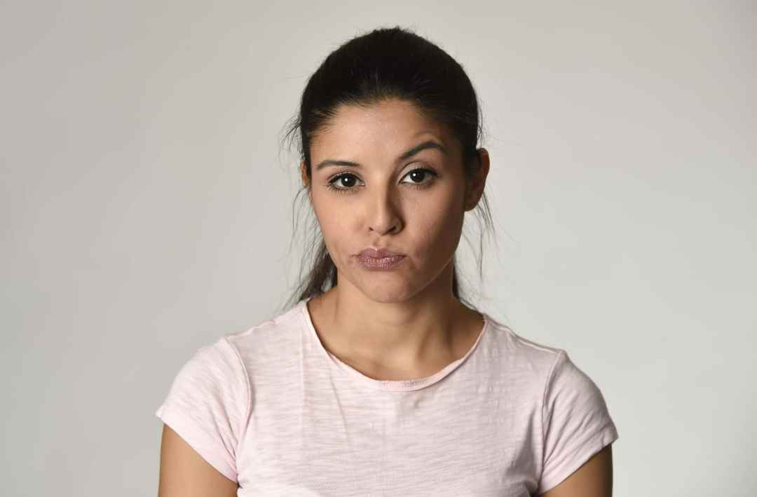 Eine junge Frau mit schwarzen langen Haaren schaut in die Kamera und zieht die Mundwinkel hoch. Sie zeigt damit, dass sie wenig Selbstwertgefühl hat und dieses mit Hypnose aufbauen möchte.