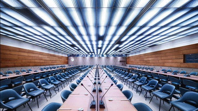 imagem de uma sala de reuniões da ONU onde acontecem os encontros do Conselho de Direitos Humanos. A sala está vazia, apenas cadeiras pretas,mesas e microfones de mesa aparecem na foto
