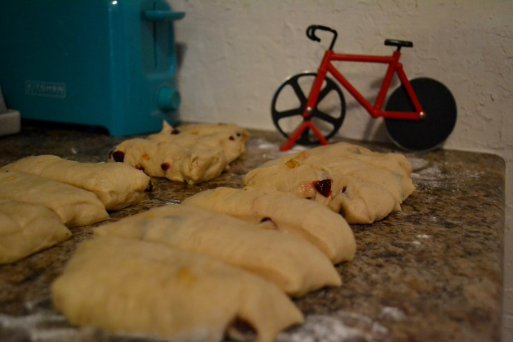 Cranberry Orange Hot Cross Buns dough after being cut with bicycle pizza cutter in background
