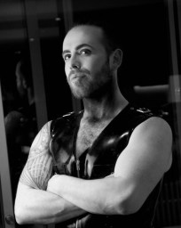 Confident bearded man in latex waistcoat with arms crossed