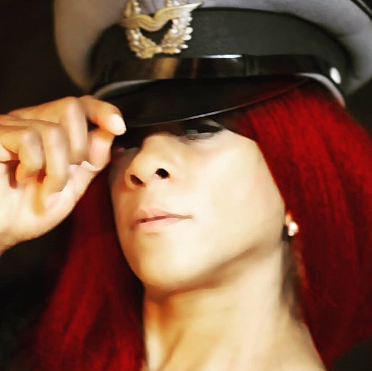 Dominant woman with red hair in a hat