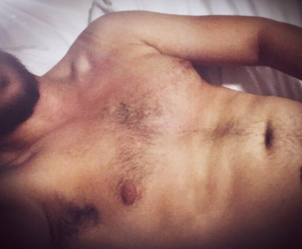 A young man's torso reclines on a bed