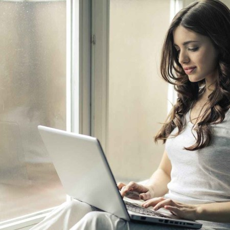 long haired brunette woman looking at laptop