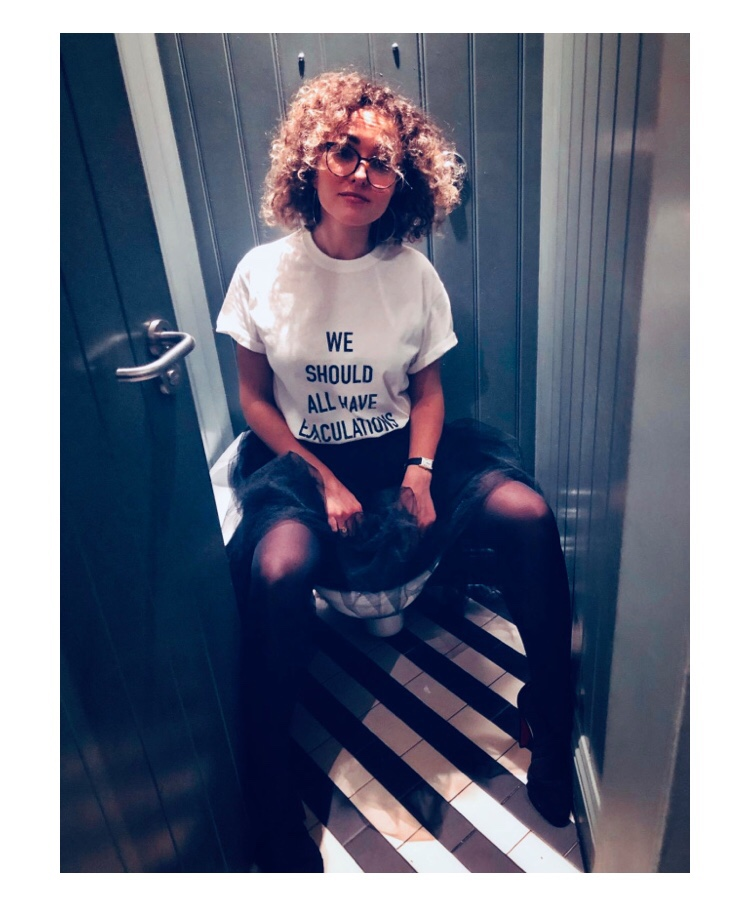 Photo of Sophie mona who runs Risqué sitting on toilet wearing 'we should all have ejaculations' t shirt