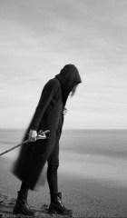 man in cloak on beach