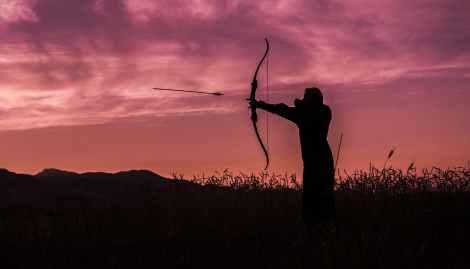Silhouette of an archer at sunset firing an arrow