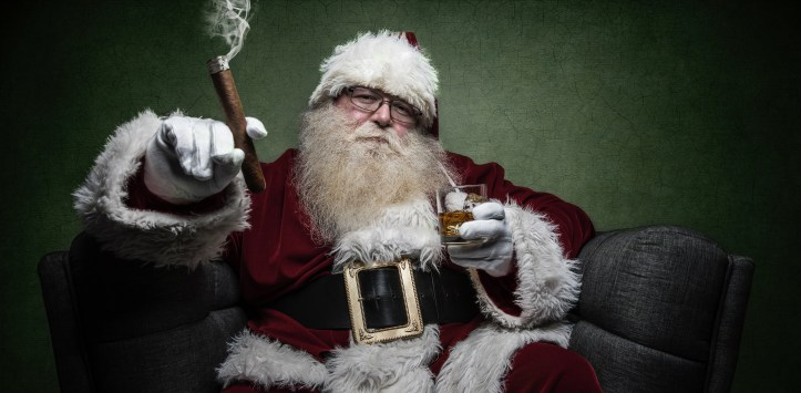 Santa sits in an armchair smoking a cigar and drinking whiskey