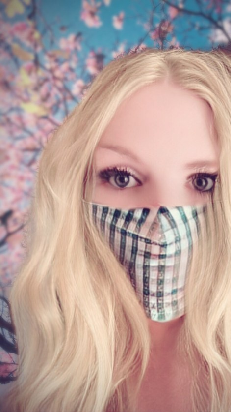 Beautiful blonde in a face mask under a cherry tree