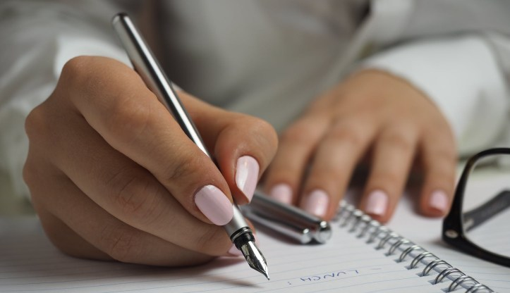 woman's hands with pink fingernails writing