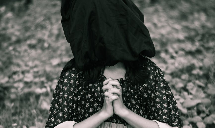 woman in black and white dress with a black bag over her head