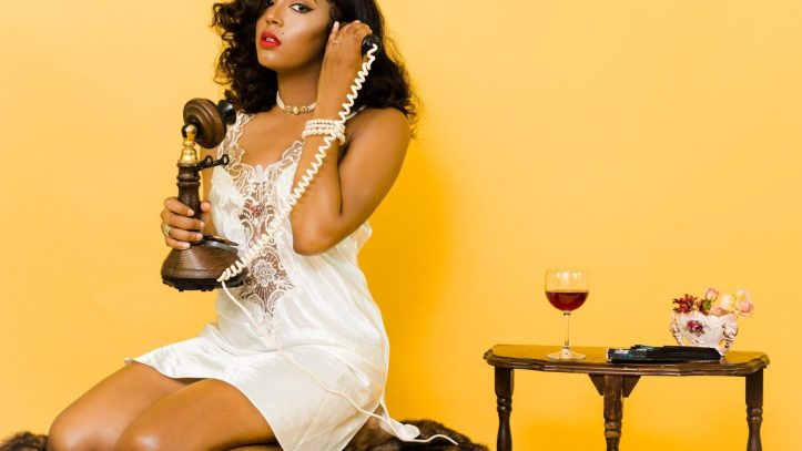 black woman in white dress calling in telephone wearing white lingerie