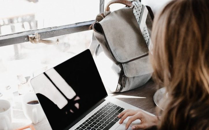 close up photography of woman sitting beside table while using macbook. is she an online content creator?