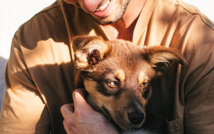 crop man with puppy in hands.  So much better than a dick pic.