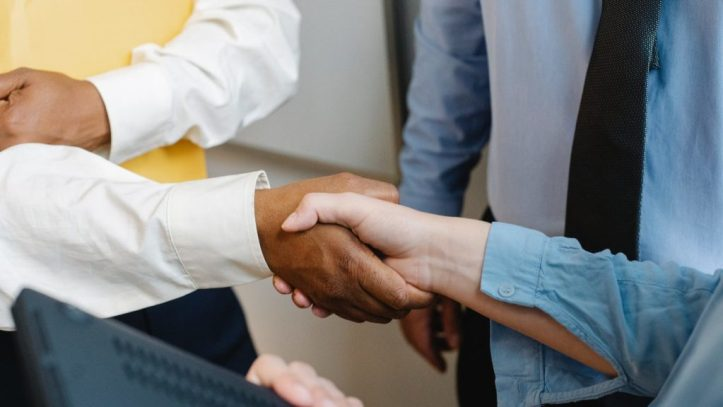 multiracial colleagues shaking hands at work.  Common ground can often be found where it seems there was none.  Can a vaccinated person and an antivaxxer both agree that they don't trust the government?