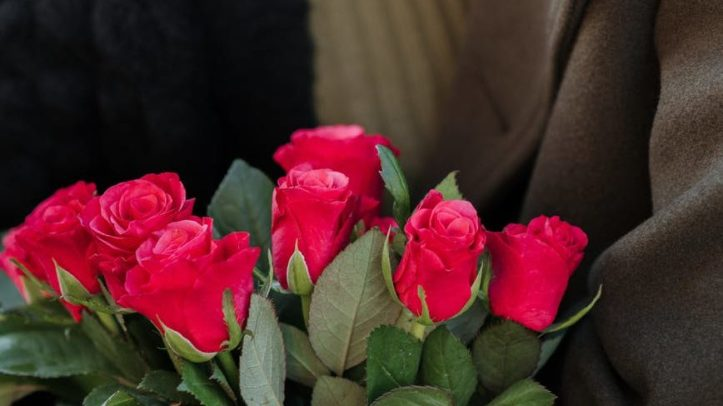 crop couple with bunch of roses embracing on street